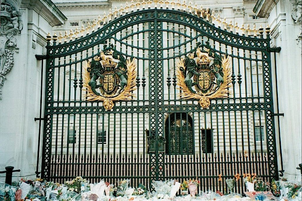 Image shows the decorative gates to Buckingham Palace. In the foreground are a number of bunches of flowers.