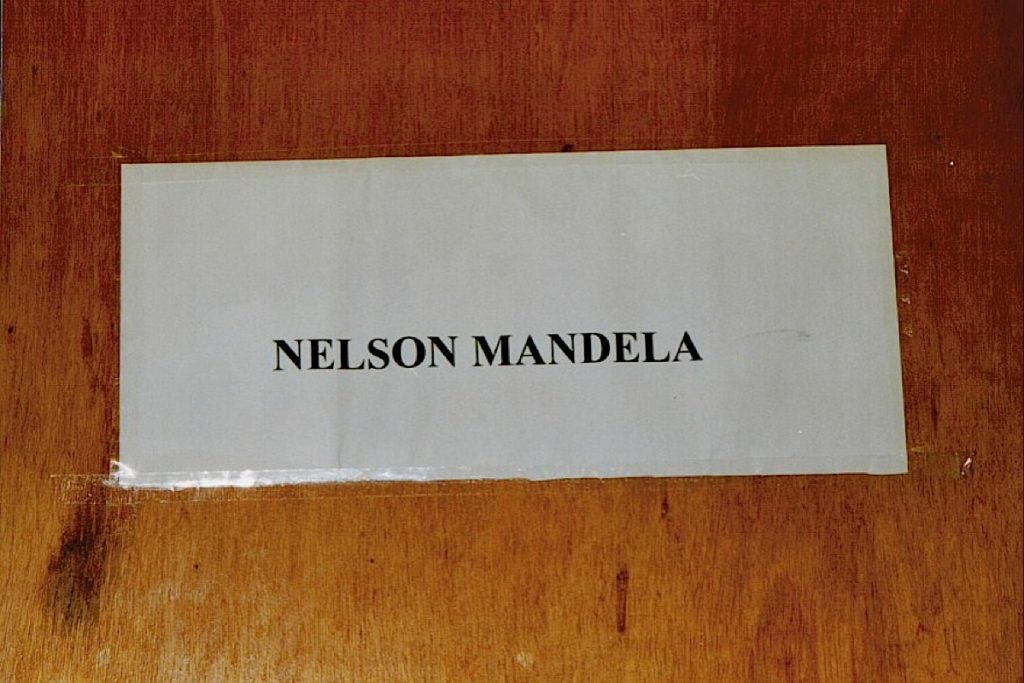 Image shows the name Nelson Mandela on a prison cell wall