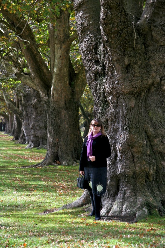 Mardi in foreground in black dress and pink scarf stanging in front of tree.  Behinf her off at an angle are several other trees in line