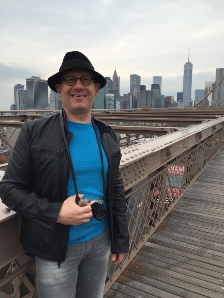 Image of Michael in New York, skyline of Manhattan in background.