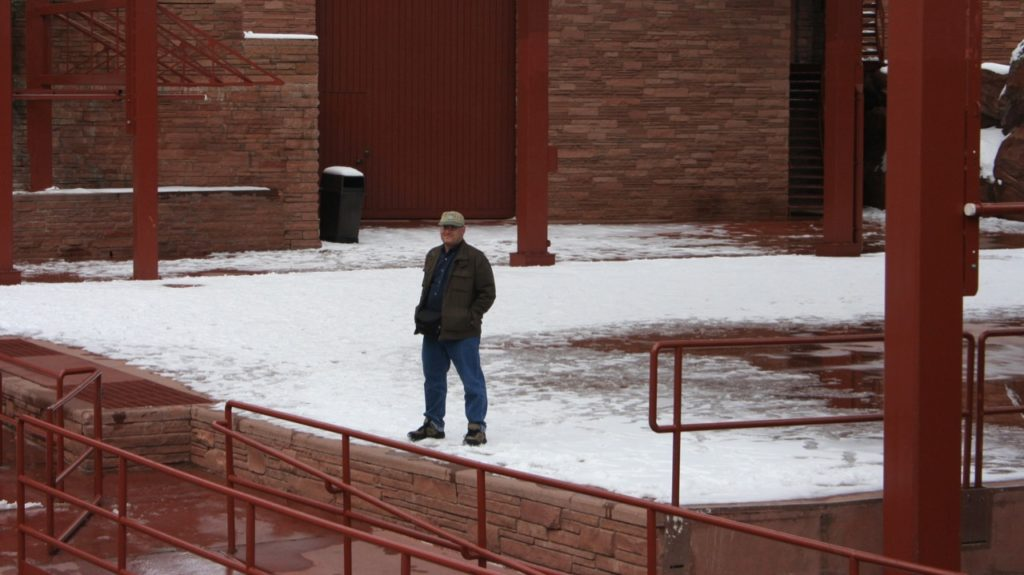 Image taken from a distance of me, standing on the centre of the stage at Red Rocks. The stage is covered in snow.