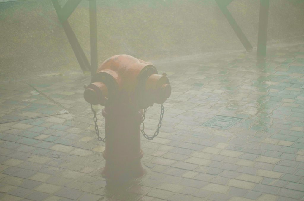 A lone fire hydrant sits in driving rain
