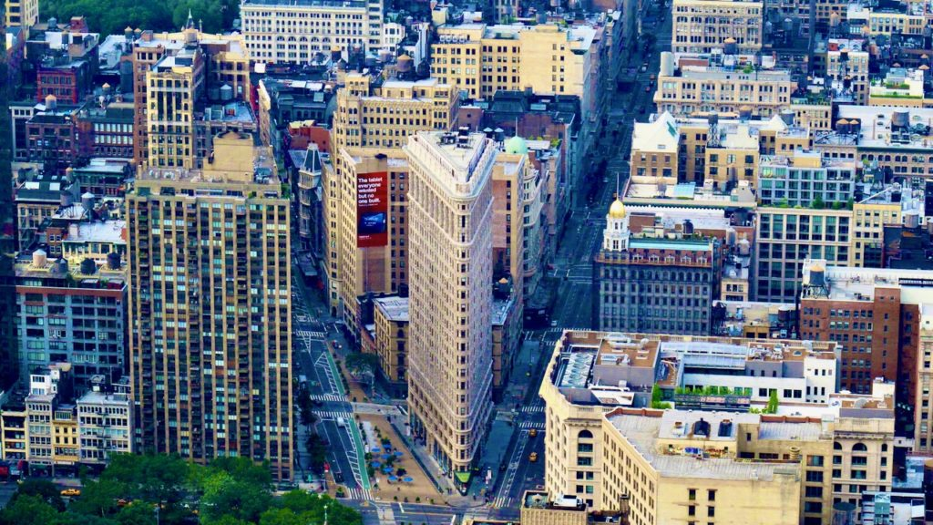 Image of the Flatiron Building in NYC from above and a distance away.  The flatiron thin edge faces forward and two streets fan out.  Other buildings fill the frame.behind it.
