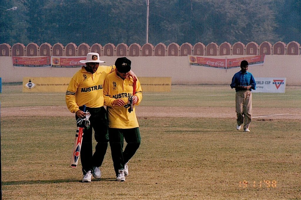A picture of a cricket field, with me and Nejat in the foreground leaving the field. A lone Sri Lankan cricketer is in the background. The field is heavy with smog.