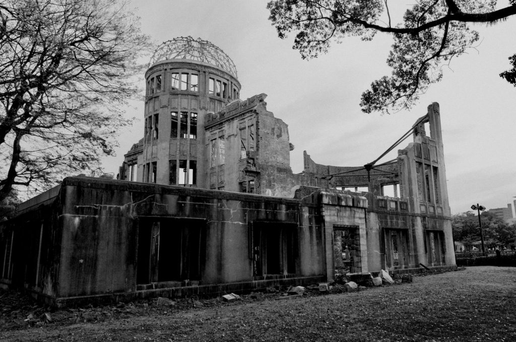 Black and white image of the peace dome in Hiroshima. Trees bound the image which shows the damaged dome and structures.