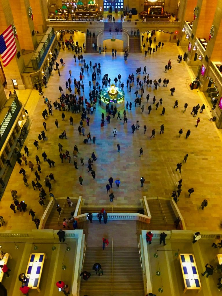 Image form internally above Grand Central.  Showing people going about their business on the ground. The vast windows at the far end cast a blue glow on the ground